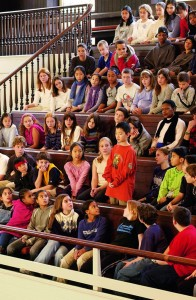 A Friends Select School student in the balcony of the Race Street stands to give vocal ministry while students seated nearby look on.
