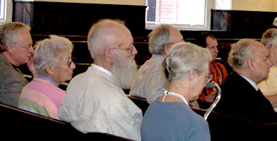 A group of Quakers sits on benches during meeting for worship.