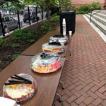 Image of tables with food and lemonade on them, in a brick courtyard in front of the Race Street Quaker Meetinghouse