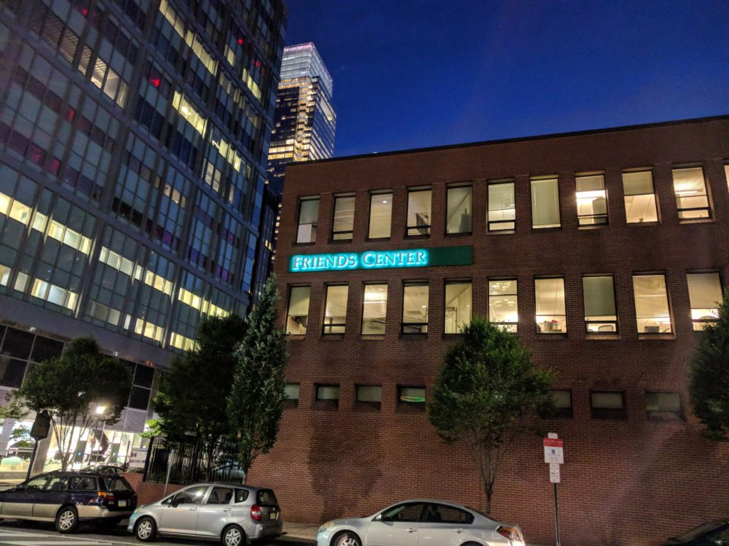 "Early evening photo of Friends Center's 1501 Cherry Street building, with a new sign saying ""Friends Center"" with letters backlit by LED lamps."