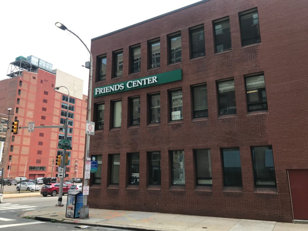 "Photo of Friends Center's 1501 Cherry Street building, with a new sign saying ""Friends Center"" in white letters on a green background on the brick wall."
